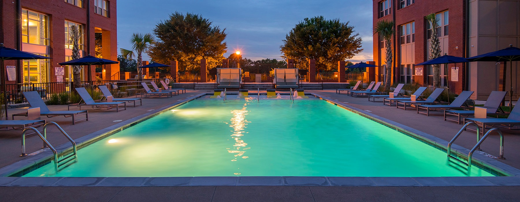 well lit outdoor pool at night surrounded by lounge chairs